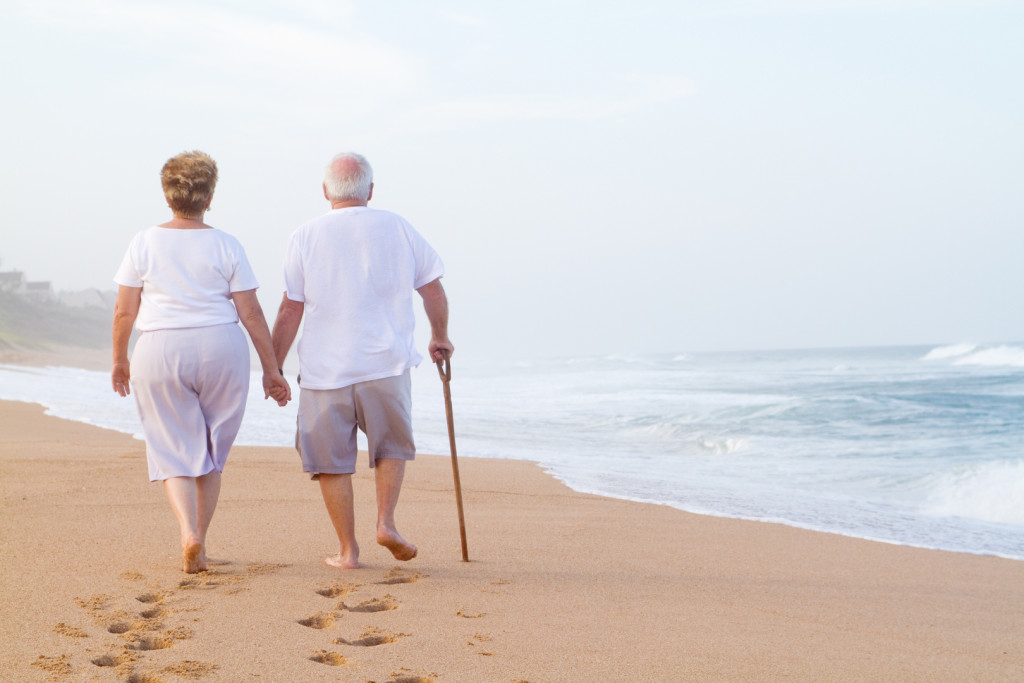 senior couple hand in hand walking on beach